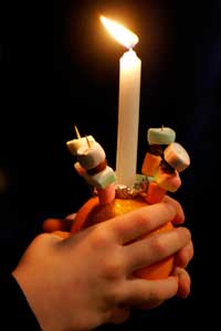 Picture of a lighted Christingle held in a child's hands